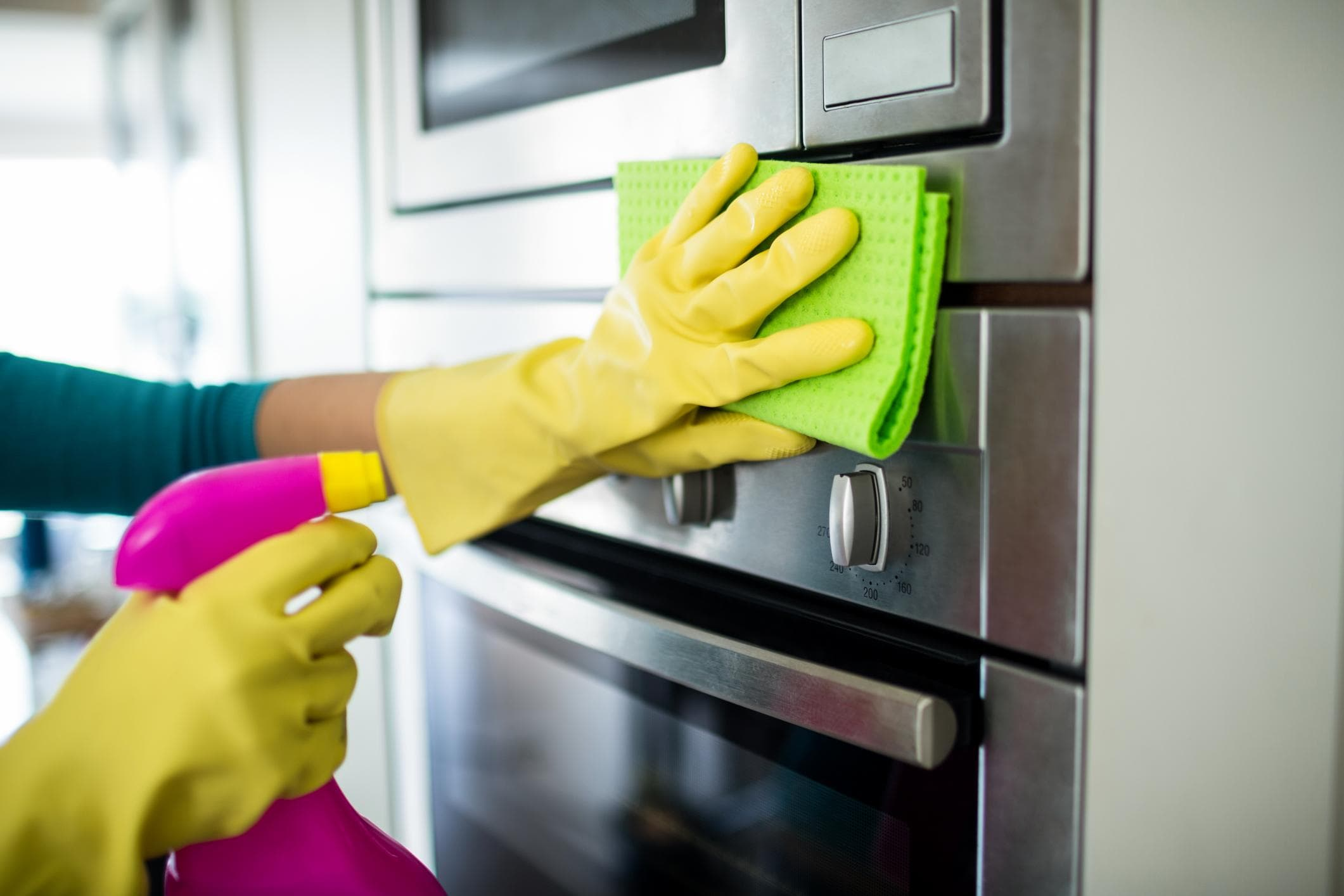 a picture of person wiping on the kitchen appliance using a spray and a piece of cloth